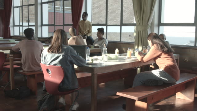 college students sit in dining hall, medium shot - canteen stock videos & royalty-free footage