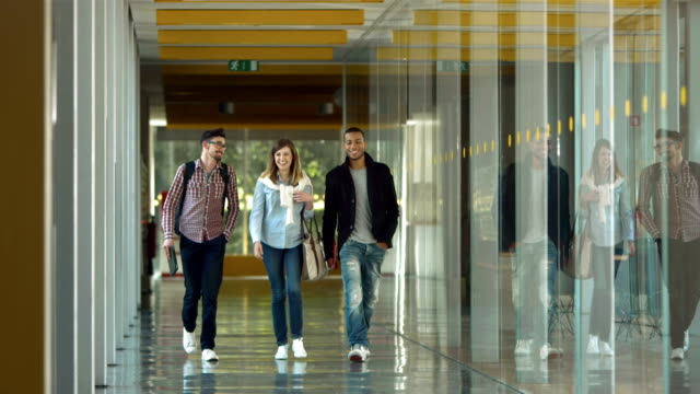 stockvideo's en b-roll-footage met slo mo ds college students walking in the corridor - dichterbij komen