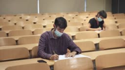 College students wearing face masks attend lecture at the University. Social Distancing measures and empty classroom due to Coronavirus Pandemic