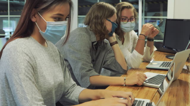 college students wearing face masks working together in computer lab setting 4 k video - post secondary education stock videos & royalty-free footage