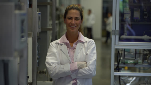 vídeos de stock e filmes b-roll de college teacher at the chemistry lab smiling at camera with arms crossed - glove