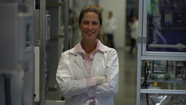 vídeos y material grabado en eventos de stock de profesor universitario en el laboratorio de química sonriendo a la cámara con los brazos cruzados - guantes de protección