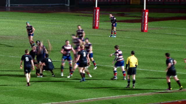 college university student rugby match line out at night in stadium on grass pitch. no audio - ナイトイン点の映像素材/bロール