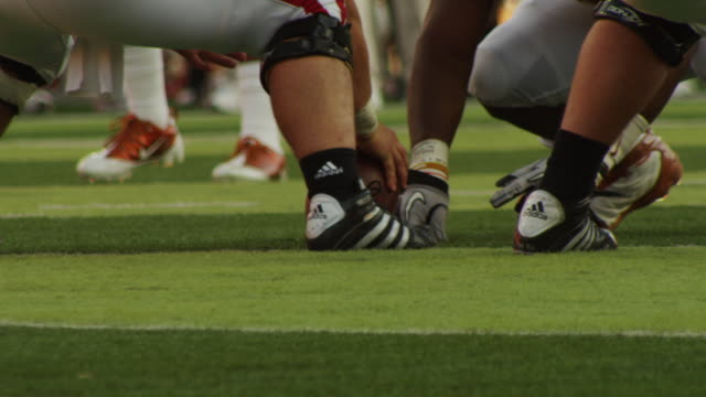 Collegiate football teams on the line, closeup of center holding ball; he hikes it to quarterback.