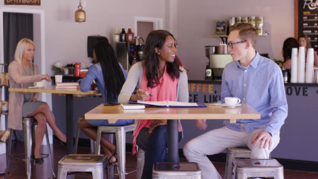 collegiate students working together in a coffee shop - fatcamera stock videos & royalty-free footage