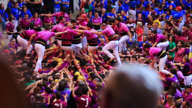colles de castellers are building different castells are tall human towers during the bianual concurs de castells competitions in tarragona - menschlicher arm stock-videos und b-roll-filmmaterial
