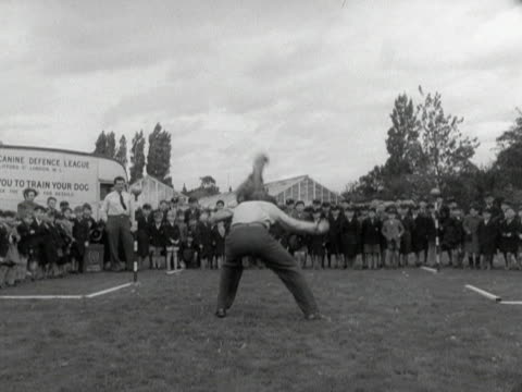 collie dog jumps through the arms of an instructor during a demonstration by the national canine defence league. 1950. - jumping stock videos & royalty-free footage