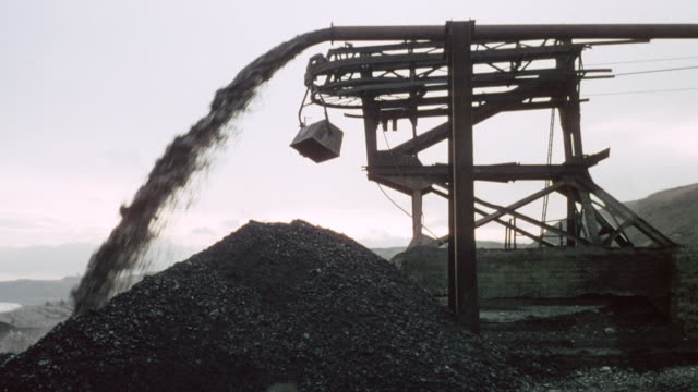 1978 montage colliery pipeline pouring water onto beach beside pile of coal as bulldozer drives by / durham, england, united kingdom - durham england stock-videos und b-roll-filmmaterial