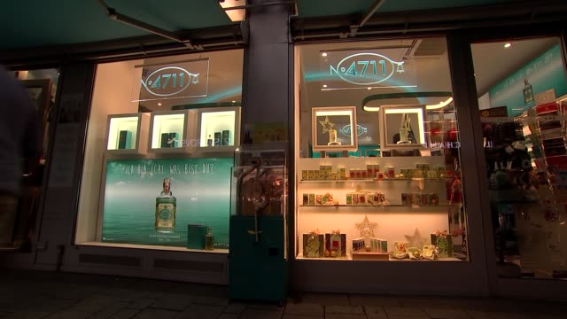 Cologne general views / Ford factory Signpost / people along through square / 'Original Eau de Cologne' shopfront / various perfumes / Christmas...