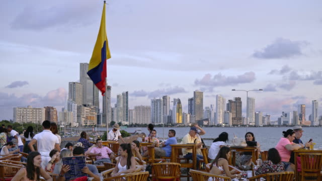 colombian flag at cafe del mar with skyline of bocagrande - colombia stock videos & royalty-free footage
