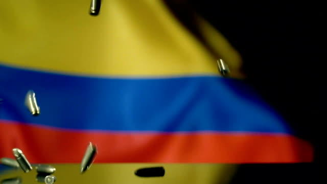 colombian flag behind bullets falling in slow motion - colombian flag stock videos and b-roll footage