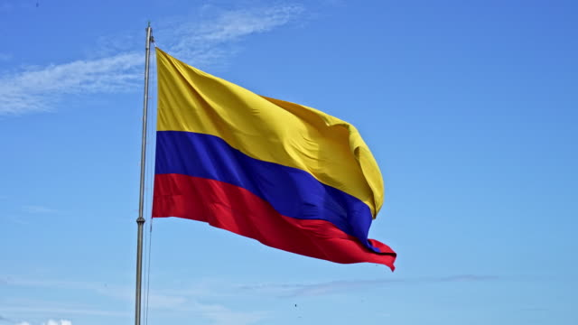 colombian flag on blue sky - colombian flag stock videos and b-roll footage