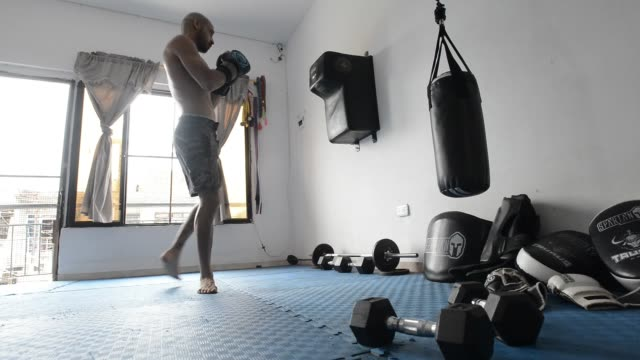 colombian mixed martial arts fighter jc fernandez punches a punching bag as he trains at home during the governmentordered lockdown to halt the... - home workout stock videos & royalty-free footage