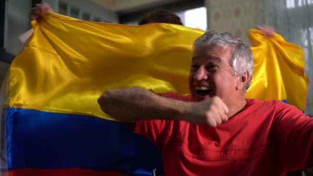 Colombian senior couple fan watching soccer game at home