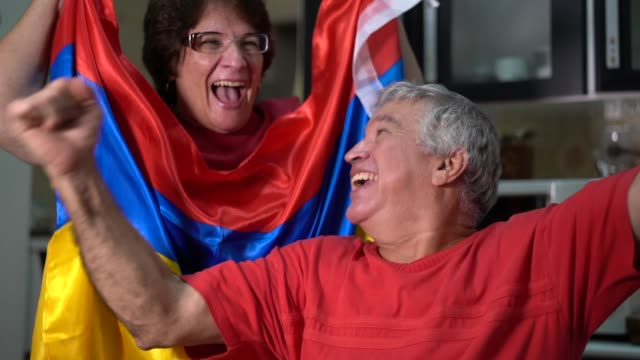 colombian senior couple fan watching soccer game at home - fan enthusiast stock videos & royalty-free footage
