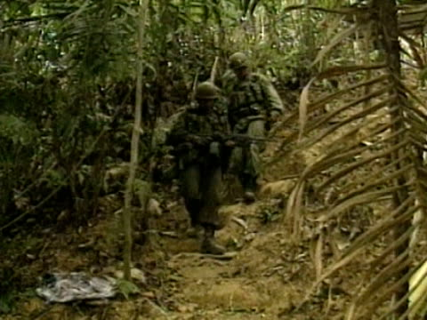 colombian soldiers approach a cocaine factory hidden in jungle colombia 1990s - 麻薬点の映像素材/bロール