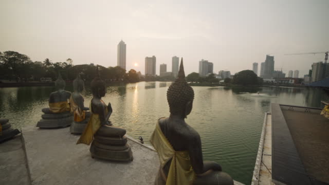 Colombo, Sri Lanka, Iconic image dolly shot. Seema Malaka buddhist temple at sunset in Beira lake and Colombo skyline on the background
