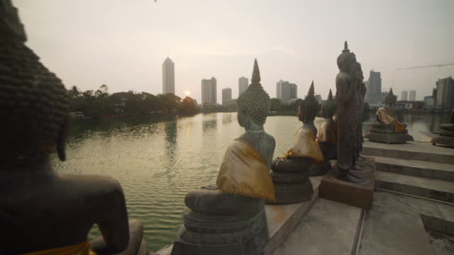 colombo, sri lanka, iconic image. seema malaka buddhist temple at sunset in beira lake and colombo skyline on the background - newly industrialized country stock videos & royalty-free footage