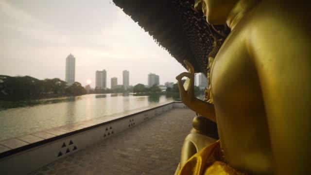colombo, sri lanka, iconic image. seema malaka buddhist temple at sunset in beira lake and colombo skyline on the background - sri lankan culture stock videos & royalty-free footage