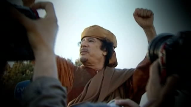 analysis of gaddafi's reign tx 1042011 gaddafi waving fists with photographers in the foreground - muammar gaddafi stock videos & royalty-free footage