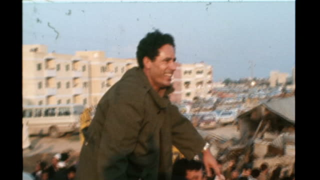 vídeos de stock, filmes e b-roll de analysis of gaddafi's reign tx tripoli shots of gaddafi atop vehicle waving to crowds burning slums - líbia