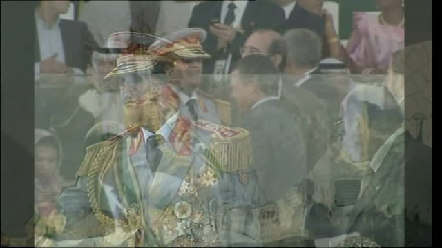 colonel muammar gaddafi behind bullet proof glass at ceremony to mark 40th anniversary of coup reporter to camera with gaddafi in background on stage - muammar gaddafi stock videos & royalty-free footage