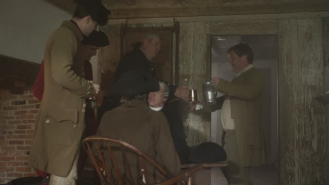Colonial era men drink in tavern