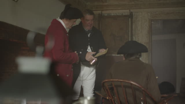 colonial gentlemen talking and reading papers in tavern - colonial reenactment stock videos & royalty-free footage