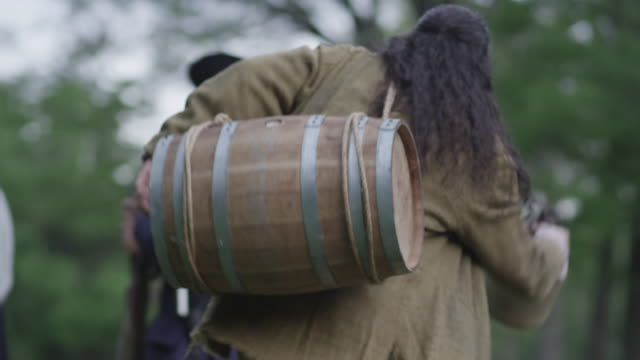 Colonial man carrying barrel