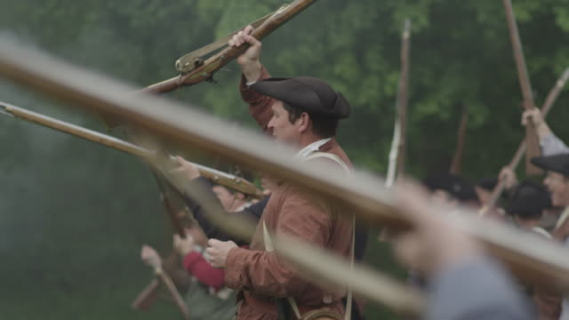 colonial soldiers during a revolutionary war reenactment raise their muskets and fists on a battlefield. - colonial reenactment stock videos & royalty-free footage