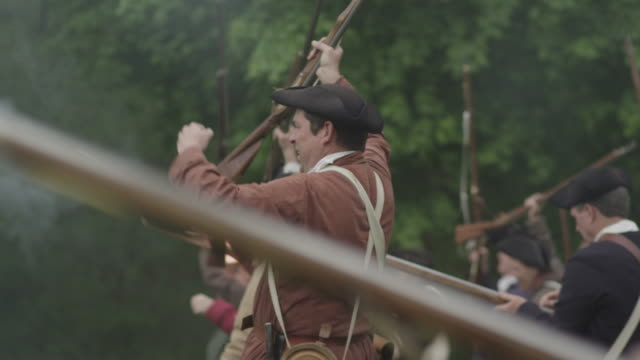 colonial soldiers during a revolutionary war reenactment raise their muskets in victory. - colonial reenactment stock videos & royalty-free footage