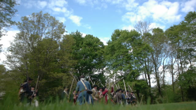 colonial soldiers retreat while firing muskets during a reenactment of a revolutionary war battle. - colonial reenactment stock videos & royalty-free footage