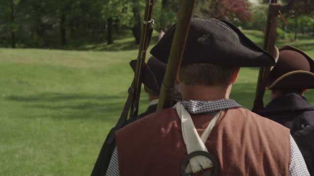 colonial soldiers with tricorn hats and muskets march toward british soldiers during a revolutionary war reenactment. - colonial reenactment stock videos & royalty-free footage