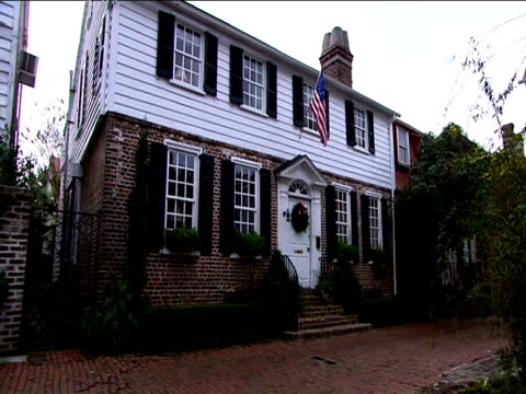 Colonial-looking house with American flag and Christmas wreath on door