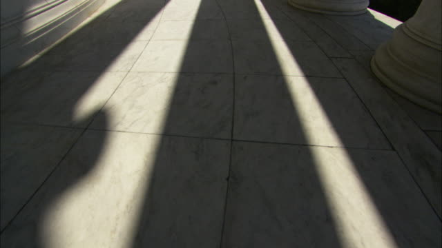 a colonnade casts long shadows on the interior floor of jefferson memorial in washington, d.c. - colonna architettonica video stock e b–roll