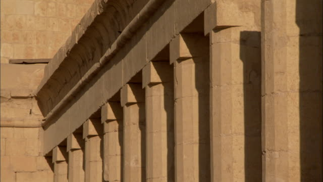 vídeos de stock, filmes e b-roll de a colonnade runs along the front of the temple-of-hatshepsut in egypt. available in hd. - templo de hatshepsut