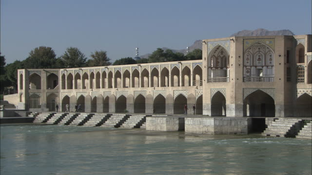 WS PAN Colonnades and arches of Khaju Bridge with jagged mountains in background / Isfahan, Iran