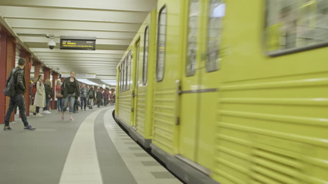stockvideo's en b-roll-footage met color footage of a subway train arriving to a platform at alexanderplatz station. - metro passagierstrein