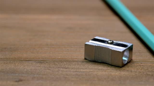 vídeos y material grabado en eventos de stock de lápices de colores y sacapuntas de lápiz sobre tabla de madera de la textura, panning video - sacapuntas