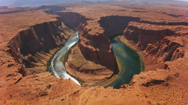 aerial colorado river scheint in der sonne und läuft um den horseshoe bend in arizona, usa - grand canyon stock-videos und b-roll-filmmaterial