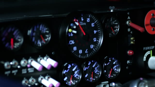 focus 7 colored gauges w/ blinking lights on dashboard near switches indicator hands of gauges spin rapidly then stop end soft focus nascar... - speedometer stock videos & royalty-free footage