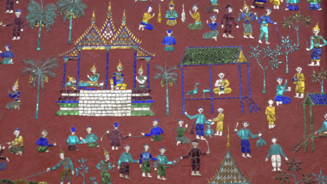 colored glass mosaics at the library at buddhist temple wat xieng thong - mythologie stock-videos und b-roll-filmmaterial