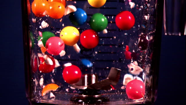 colored gum balls break as they hit the blades of a blender. - physics stock videos & royalty-free footage