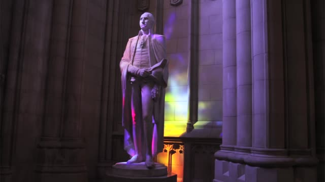 vídeos de stock e filmes b-roll de colored lights shine through stained glass windows onto a statue of george washington at the washington national cathedral washington dc july 1 2015 - george washington