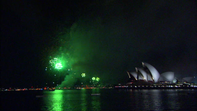 colorful and continuous fireworks explode and flash over sydney harbor and the sydney opera house during a new year's celebration. - オペラ座点の映像素材/bロール