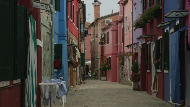Colorful apartments along city street / Burano, Italy