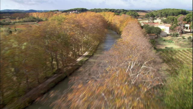 colorful autumn-hued trees line canal du midi in a rural area near ouveillan, france. - canal du midi stock videos & royalty-free footage