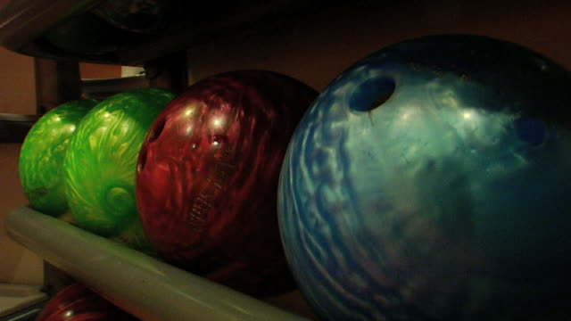 stockvideo's en b-roll-footage met ms colorful bowling balls on rack in unidentifiable bowling alley sports equipment - bowlingbal