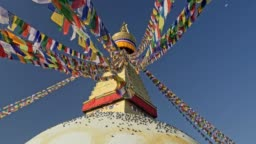 Colorful Buddhist flags and the Boudhanath stupa in Kathmandu, Nepal. 4K, UHD