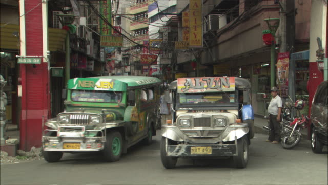Colorful buses and other traffic turn off a narrow street in Manila.